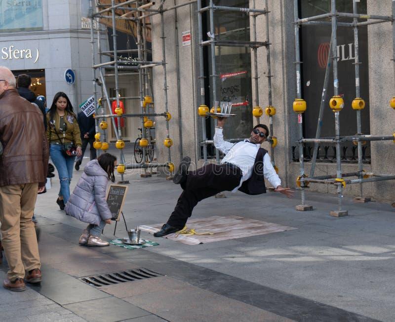 Madri, Espanha - novembro 11,2017: Dinheiro não identificado dos lugares das moças em uma cubeta dos executores da rua perto de P foto de stock royalty free