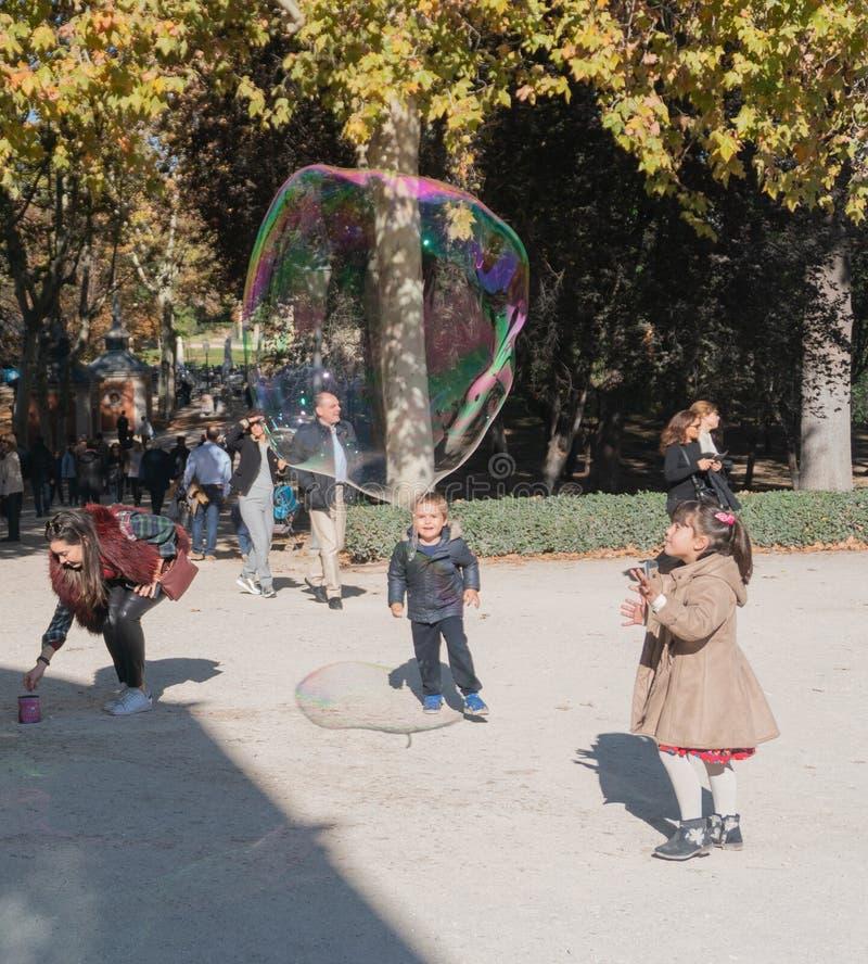 Madri, Espanha - novembro 12,2017: Jogo de crianças não identificado novo com bolhas no Madri do parque de Retiro, Espanha imagem de stock royalty free