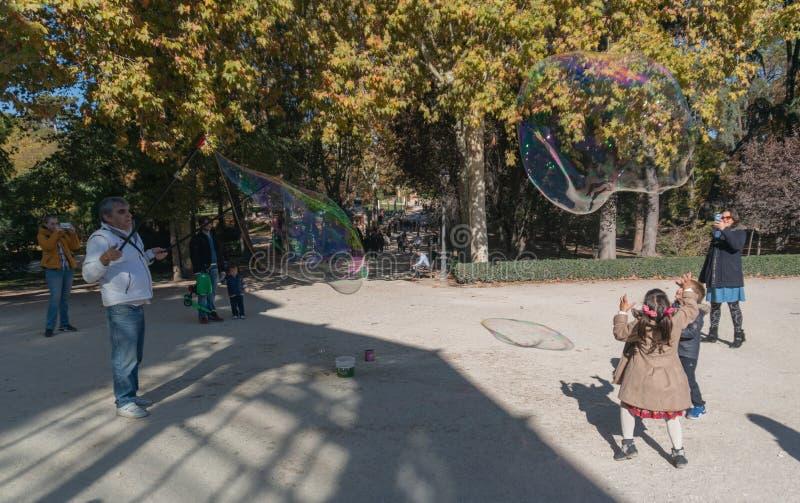 Madri, Espanha - novembro 12,2017: Jogo de crianças não identificado novo com bolhas no Madri do parque de Retiro, Espanha imagens de stock