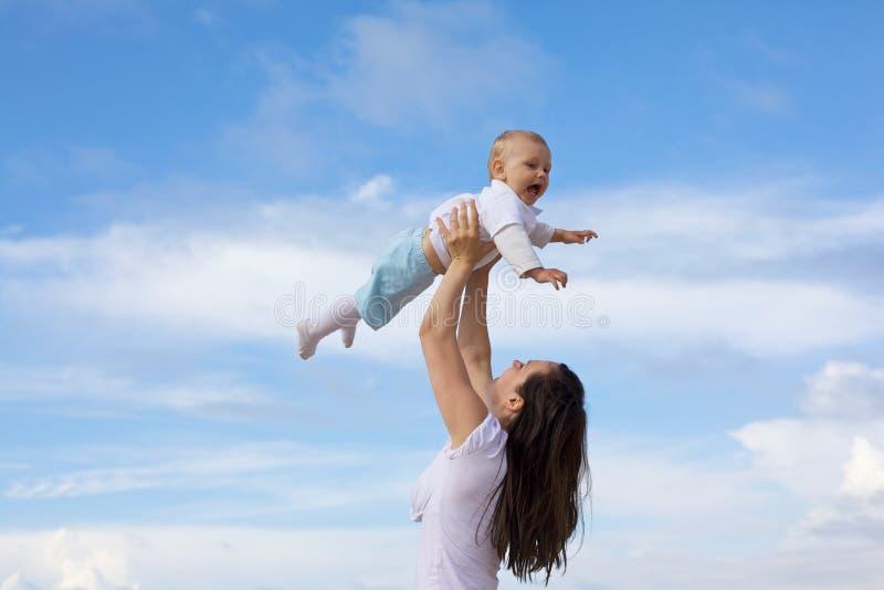 Madri felici con i bambini alla spiaggia immagini stock