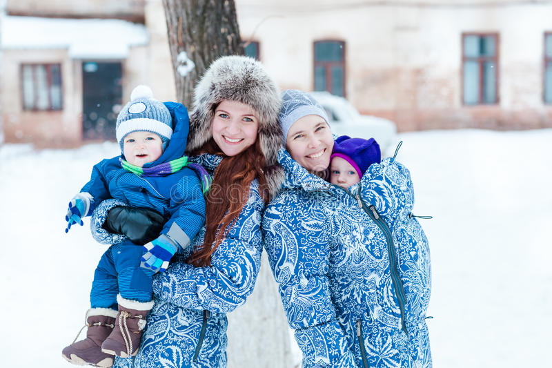Madri felici e babys che giocano sulla neve fotografie stock libere da diritti