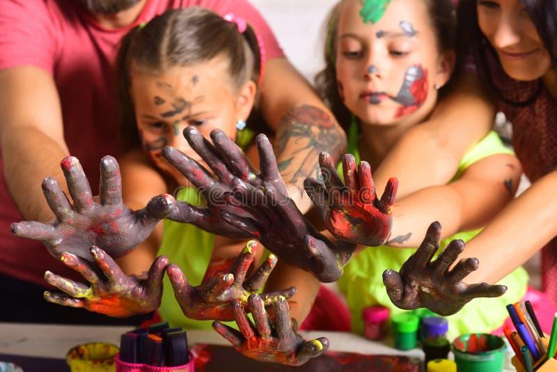 Madri, padri, mani delle ragazze colorate con le pitture fotografie stock