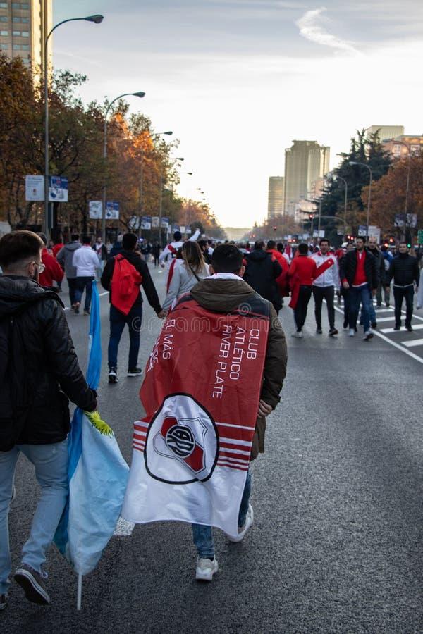 MADRID DECEMBER 09 - River Plate suporter går med en flagga på vägen i finalen av Copaet Libertadores på Bernabéu arkivfoto