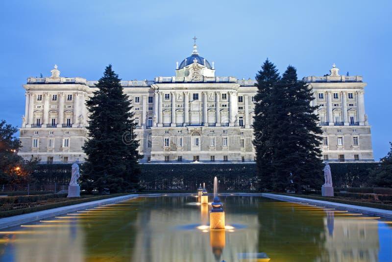 Madrid - Palacio arbeta i trädgården den verkliga eller kungliga slotten från Sabatini i skymning. fotografering för bildbyråer