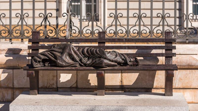 MADRID, SPAGNA - 26 SETTEMBRE 2017: Scultura di un uomo senza tetto nella via della città Copi lo spazio per testo fotografia stock libera da diritti
