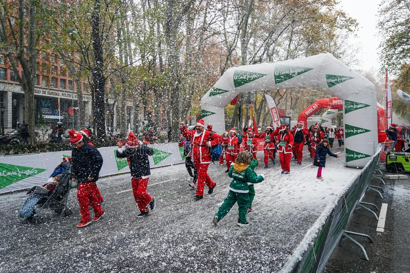 Madrid, Spain, December 8th 2019: Crowd of Santa Clauses running in street stock image