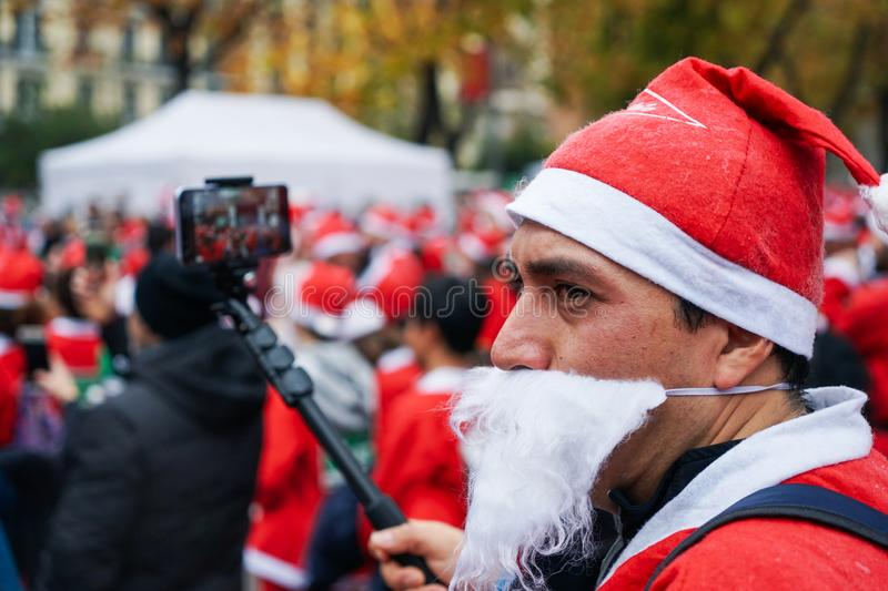 Madrid, Spain, December 8th 2019: Crowd of Santa Clauses running in street royalty free stock images