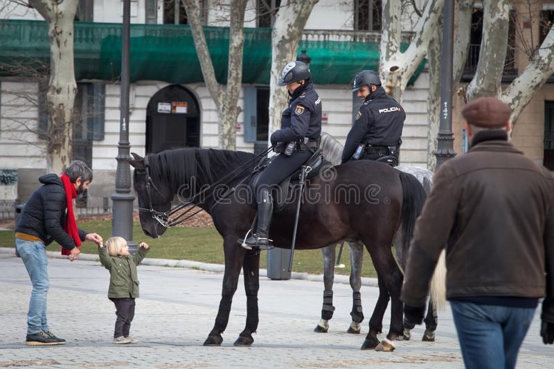 Spanish mounted police officer in Madrid, behind Royal Palace. Madrid, Spain, February 12, 2018: Spanish mounted police officer in Madrid, behind Royal Palace royalty free stock photography