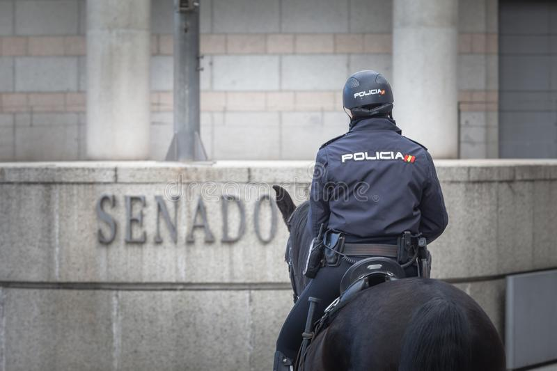 Spanish mounted policewoman officer in Madrid, behind Royal Palace. Madrid, Spain, February 12, 2018: Spanish mounted policewoman officer in Madrid, behind Royal stock images