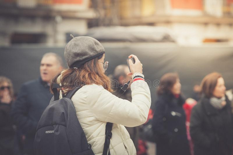 Madrid, Spain - February 12, 2018: A young tourist take photos in the Plaza Mayor, Madrid royalty free stock photo