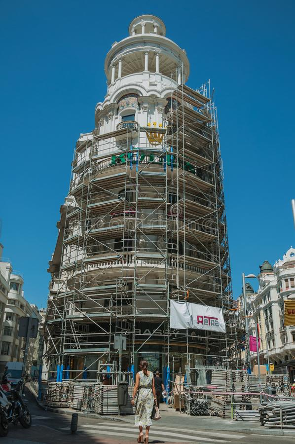 Building being refurbished with scaffolding and woman in Madrid stock photography