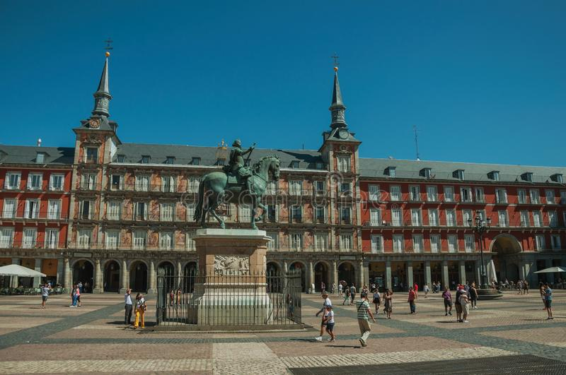 People on the Plaza Mayor with old large building in Madrid royalty free stock image