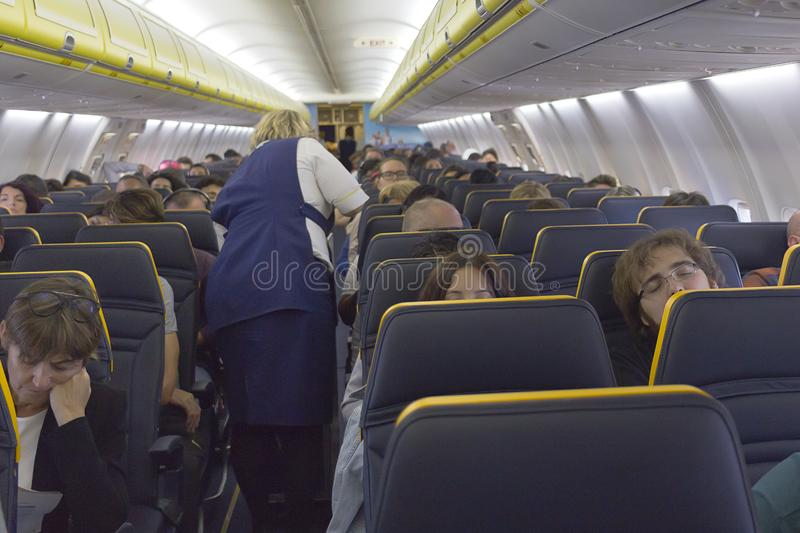 Interior of a Boeing Ryanair with passengers sit and stewardess in the aisle - Flight from Madrid to Milan - Defocused background stock images