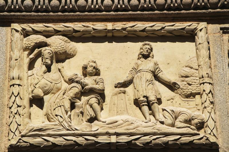 Scene carved in stone on facade of old house in Cordoba, Spain royalty free stock image