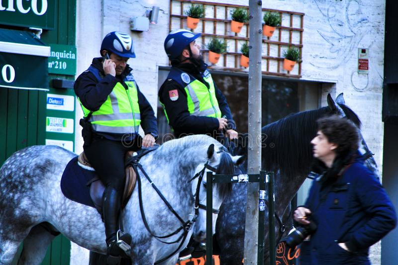 Police mounted on horseback and talking on the phone. Madrid, Spain- March 7, 2019: Police mounted on horseback and talking on the phone watching the streets of royalty free stock photos