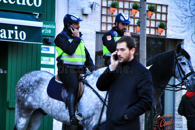 Police mounted on horseback and talking on the phone. Madrid, Spain- March 7, 2019: Police mounted on horseback and talking on the phone watching the streets of stock images