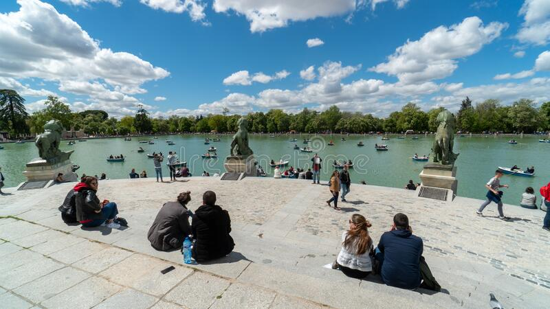 People resting and enjoying sunny weather in El Retiro Park royalty free stock image