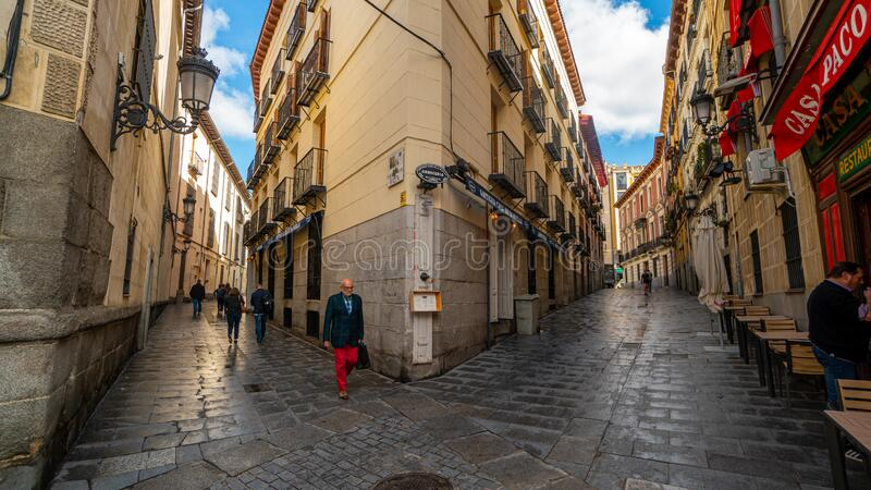 Small alley in old town with pedestrians royalty free stock photo