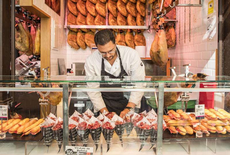 Madrid, Spain - October 7, 2017: Man Selling Iberico Ham at a Food Stall in a Market. Food Stand Selling Iberico Ham in San Miguel Market in Madrid, Spain stock image