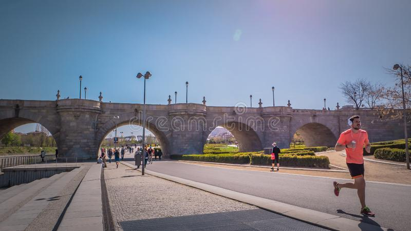 A man is running in front of the Toledo medieval bridge at Madrid Rio park in Spain stock photo
