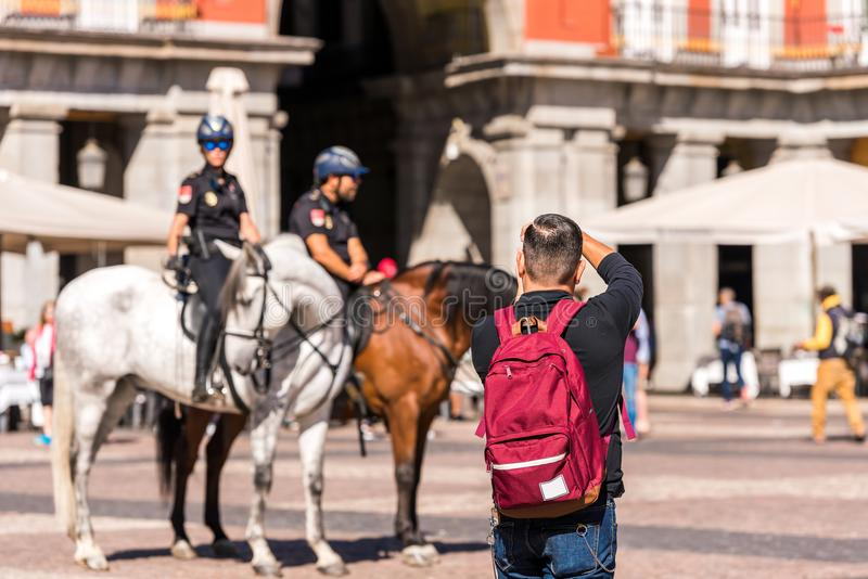 MADRID, SPAIN - SEPTEMBER 26, 2017: A man photographs the mounted police in the square of the Royal Palace building. stock images