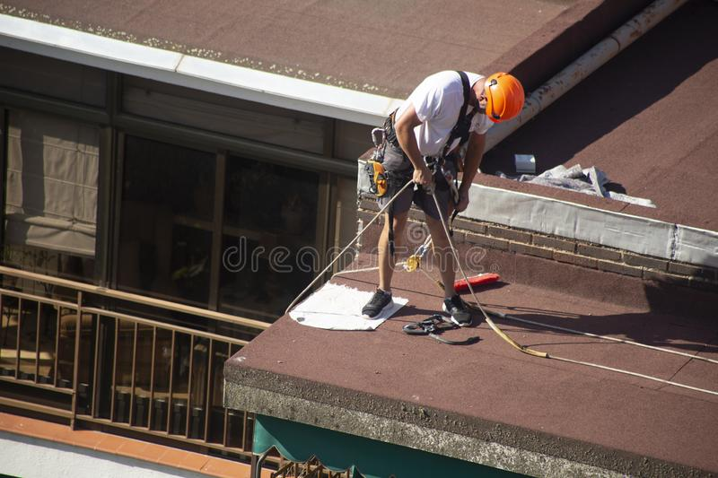 Madrid, Spain - September, 04, 2019: work at height. Worker with harness for dangerous work. A worker prepares with the helmet and harness to work at height from royalty free stock photography