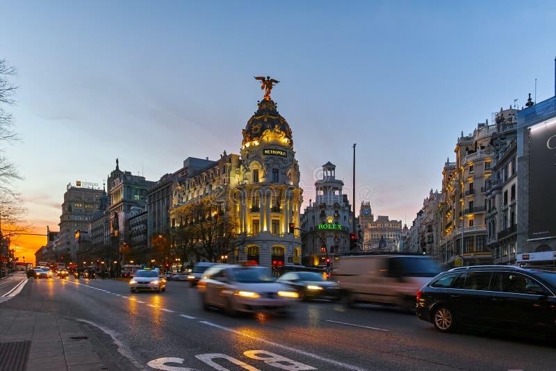 MADRID SPANIEN - JANUARI 23, 2018: Solnedgångsikt av Gran via och metropolisbyggnad i stad av Madrid arkivfoto