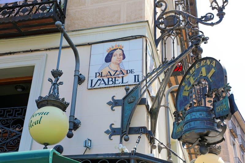 MADRID, SPANIEN - 2. JULI 2019: Schließen Sie oben vom Straßenschild quadratischen Plaza de Isabellfarbe II lizenzfreie stockfotos