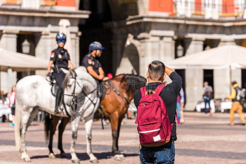 MADRID, SPANIEN - 26. SEPTEMBER 2017: Ein Mann fotografiert die berittene Polizei im Quadrat des Royal Palace-Gebäudes stockbilder