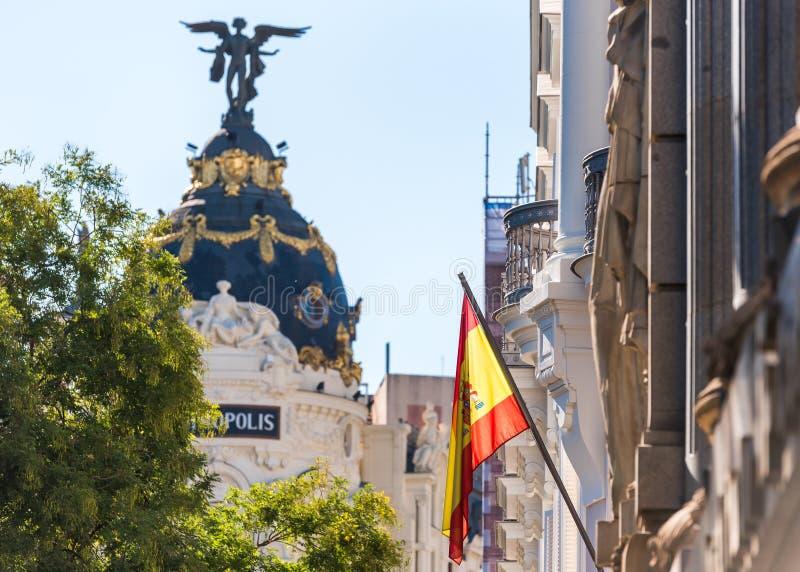 MADRID SPANIEN - SEPTEMBER 26, 2017: Sikt av den spanska flaggan på bakgrunden av metropolisbyggnaden arkivbild