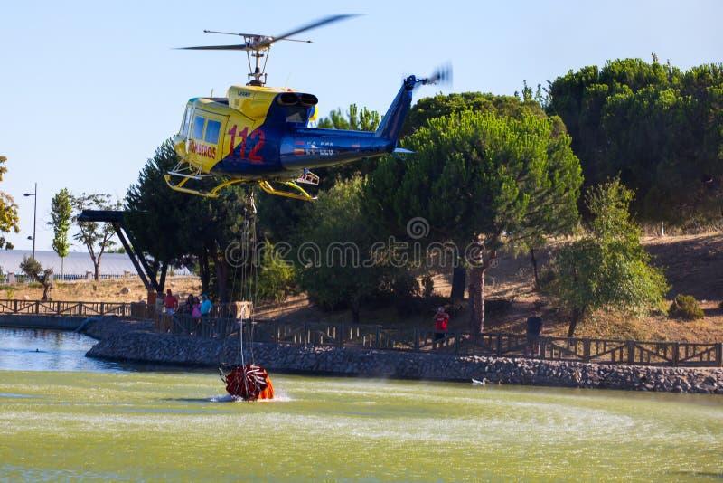 MADRID, SPANJE - AUGUSTUS 3: Gaat de zware helikopter van de brandredding met wateremmer, naar een brand in Madrid op 3 Augustus,  royalty-vrije stock afbeeldingen