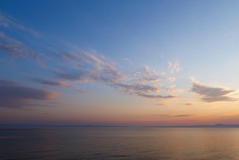 Madrugada en el amanecer del día con un overlookin azul tranquilo del mar fotografía de archivo