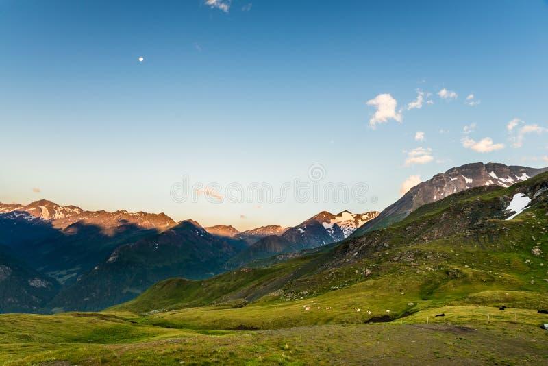 Madrugada en las montañas con los picos de montaña iluminados por el sol foto de archivo libre de regalías