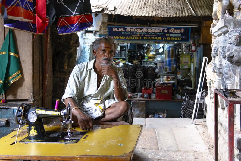 Tailor in Pudhu Mandapam market in Madurai, India. Madurai, India - August 23, 2018: A tailor in his shop sitting in front at a sewing machine in Mandapam market royalty free stock photography