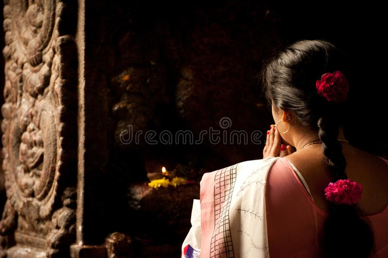Indian woman in colorful sari prays inside Meenakshi Temple, India. MADURAI, INDIA - FEBRUARY 16: Indian woman in colorful sari prays inside Meenakshi Temple on royalty free stock photo