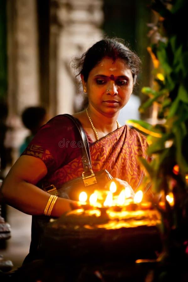 MADURAI, INDIA - FEBRUARY 16: Indian woman in colorful sari prays inside Meenakshi Temple on February 16, 2012. Meenakshi Temple stock photo