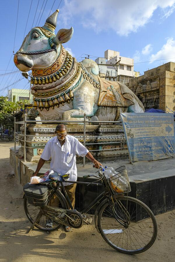 Pudhu Mandapa in Madurai, India. Madurai, India - March 2020: A man parking his bicycle next to the blue Nandi in front of the entrance to the Pudhu Mandapa on stock photos