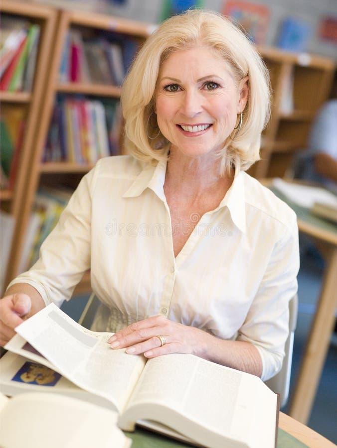 Madure al estudiante femenino que estudia en biblioteca imagen de archivo
