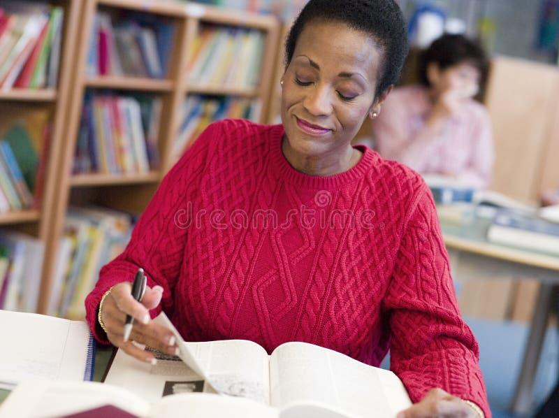 Madure al estudiante femenino que estudia en biblioteca foto de archivo