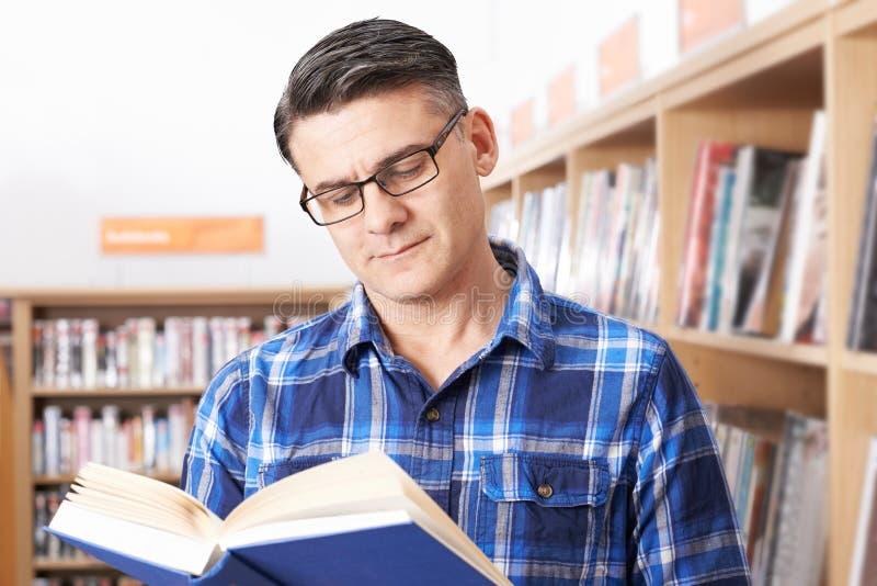 Madure al estudiante masculino que estudia en biblioteca imagen de archivo