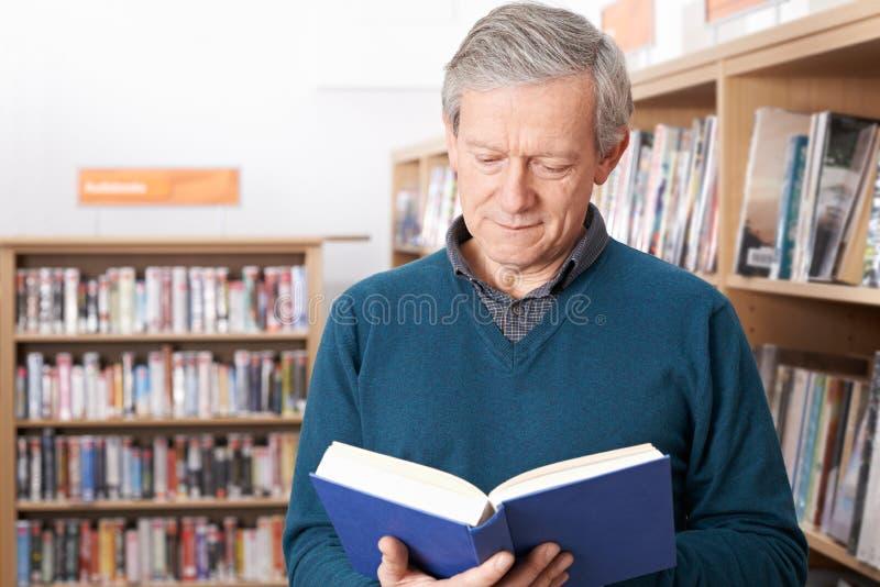 Madure al estudiante masculino que estudia en biblioteca fotografía de archivo libre de regalías