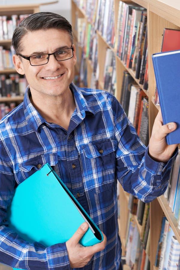 Madure al estudiante masculino que estudia en biblioteca foto de archivo libre de regalías