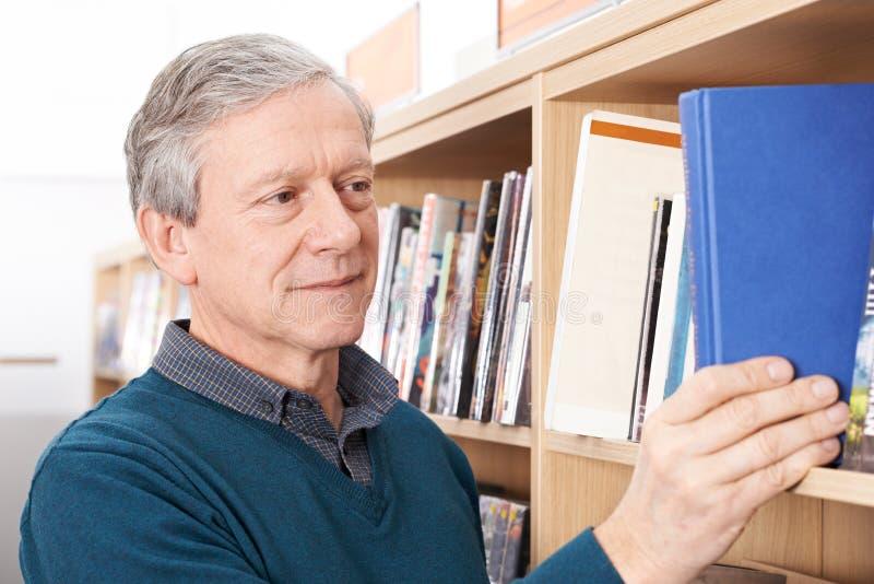 Madure al estudiante masculino que estudia en biblioteca imagenes de archivo