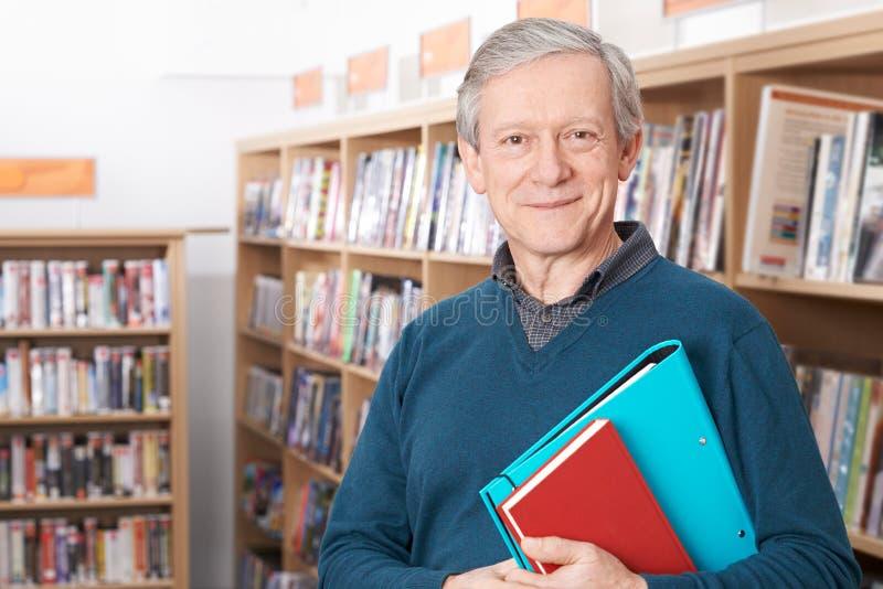 Madure al estudiante masculino que estudia en biblioteca foto de archivo