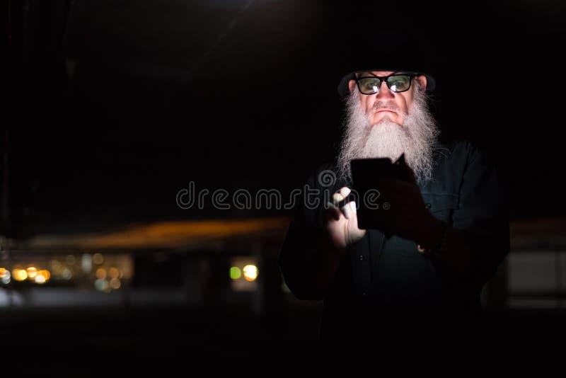 Madure al hombre barbudo que usa el teléfono y pareciendo sospechoso imagen de archivo