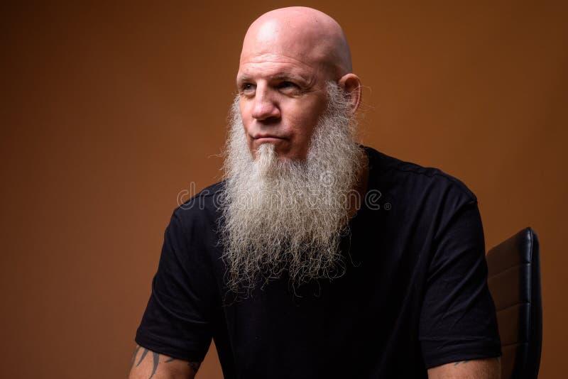 Madure al hombre calvo con la barba gris larga contra fondo marrón fotografía de archivo