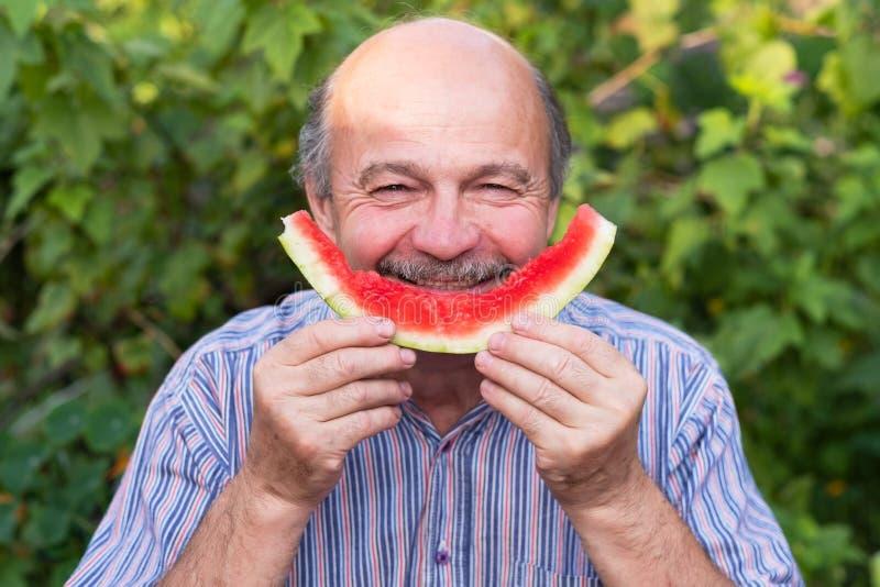 Madure al hombre caucásico con el bigote que come la sandía jugosa con placer y la sonrisa foto de archivo libre de regalías
