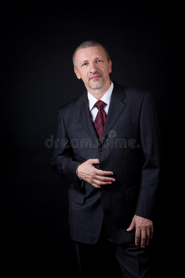Hombre de negocios maduro que lleva a cabo la mano en su juego negro imagenes de archivo