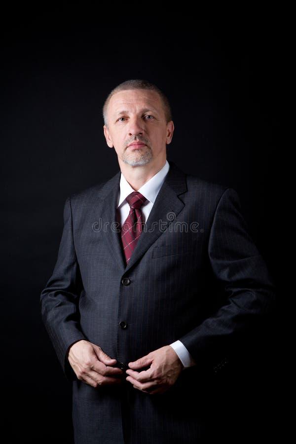 Hombre de negocios maduro que lleva a cabo las manos en su juego negro imagen de archivo