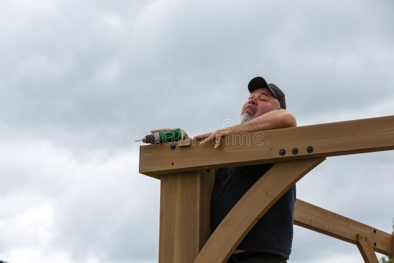 Madure al hombre que cae mientras que construye la pérgola de madera fotografía de archivo